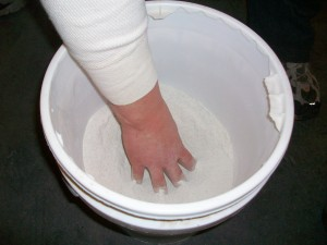 Hand extensions in bucket of sand
