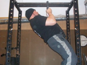 Man doing Narrow pull-ups in a gym.